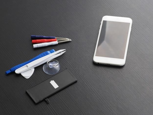 Sostituzione della batteria in un vecchio smartphone. strumenti, smartphone e batteria su un tavolo di legno.