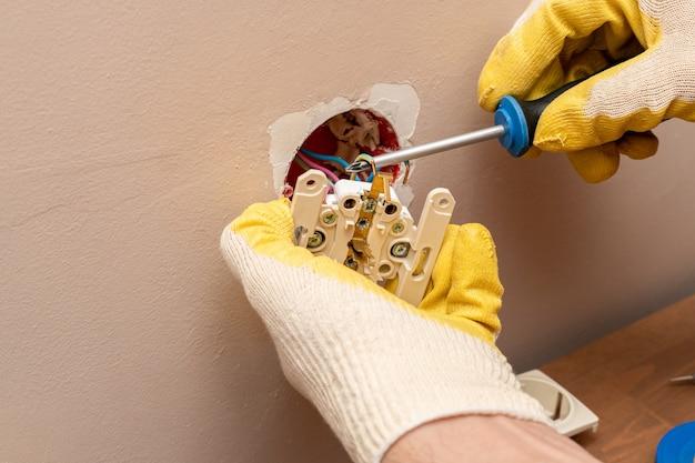 Sostituzione, installazione di una presa elettrica, presa con le mani in guanti di gomma protettivi