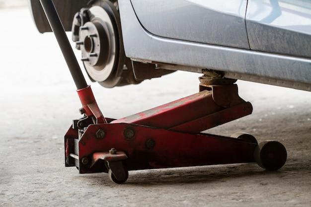 Sostituendo le ruote di un'auto, il martinetto mantiene il corpo in posizione sollevata.