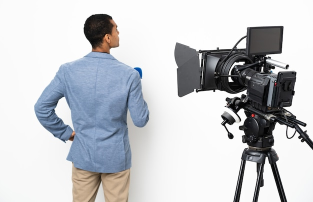 Reporter afroamericano in possesso di un microfono e segnalazione di notizie su sfondo bianco isolato in posizione posteriore e guardando il lato