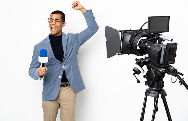 Reporter afroamericano uomo in possesso di un microfono e segnalazione di notizie su sfondo bianco isolato che celebra una vittoria