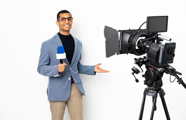 Reporter uomo afroamericano in possesso di un microfono e segnalazione di notizie su sfondo bianco isolato che estende le mani di lato per invitare a venire