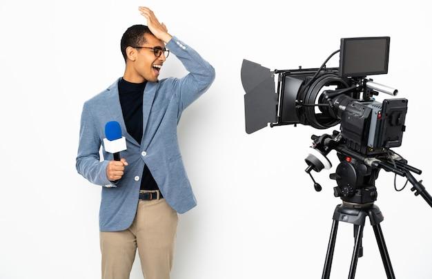 Reporter afroamericano che tiene un microfono e che riporta notizie su sfondo bianco isolato ha realizzato qualcosa e intende la soluzione