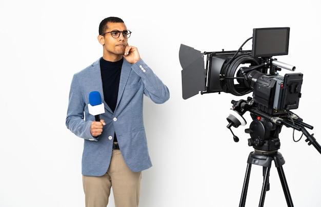 Reporter afroamericano uomo in possesso di un microfono e segnalazione di notizie su sfondo bianco isolato avendo dubbi e pensiero