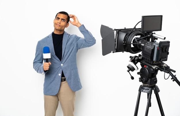 Reporter afroamericano uomo in possesso di un microfono e segnalazione di notizie su sfondo bianco isolato avendo dubbi
