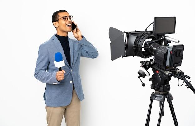 Reporter afroamericano in possesso di un microfono e segnalazione di notizie su sfondo bianco isolato mantenendo una conversazione con il telefono cellulare