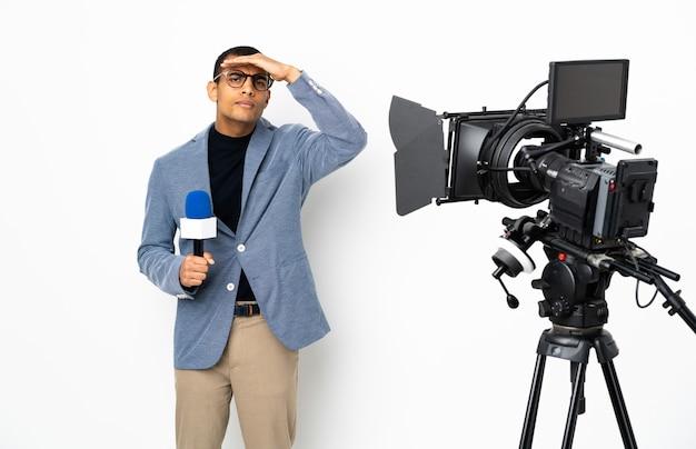 Reporter uomo afroamericano in possesso di un microfono e segnalazione di notizie su sfondo bianco isolato che guarda lontano con la mano per guardare qualcosa
