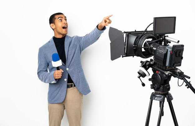 Reporter afroamericano uomo in possesso di un microfono e segnalazione di notizie su sfondo bianco isolato che punta lontano