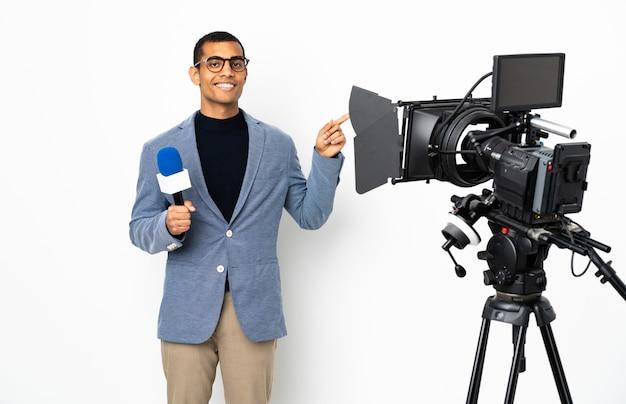 Reporter uomo afroamericano in possesso di un microfono e segnalazione di notizie su sfondo bianco isolato che punta il dito a lato