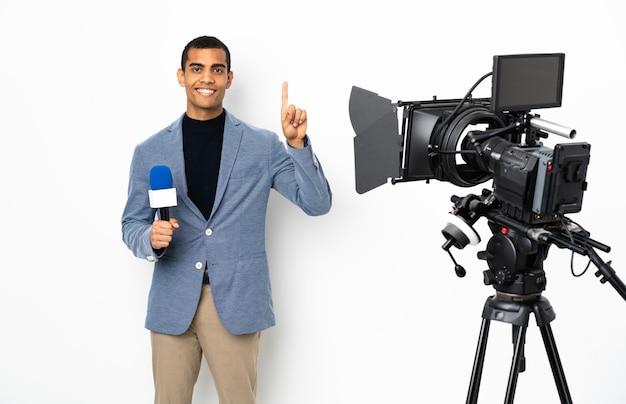 Reporter afroamericano uomo in possesso di un microfono e segnalazione di notizie su sfondo bianco isolato rivolto verso l'alto una grande idea