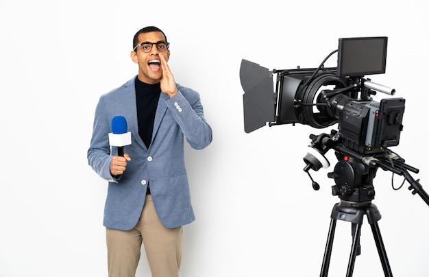 Reporter uomo afroamericano in possesso di un microfono e segnalazione di notizie su sfondo bianco isolato gridando con la bocca spalancata
