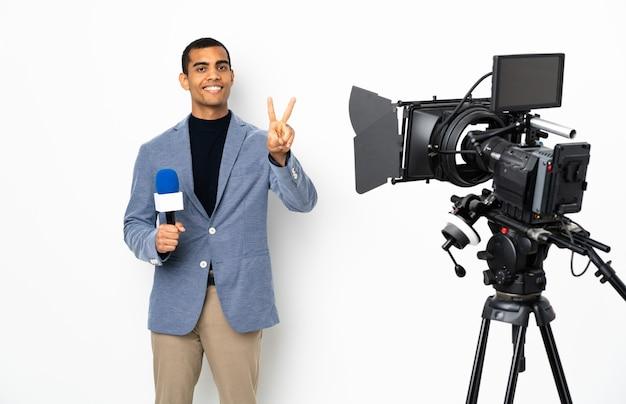 Reporter uomo afroamericano in possesso di un microfono e segnalazione di notizie su sfondo bianco isolato sorridente e mostrando il segno di vittoria