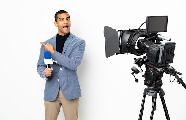 Reporter afroamericano uomo in possesso di un microfono e segnalazione di notizie su sfondo bianco isolato lato sorpreso e puntato