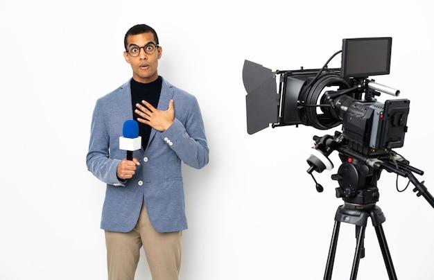 Reporter afroamericano in possesso di un microfono e segnalazione di notizie su sfondo bianco isolato sorpreso e scioccato mentre guarda a destra