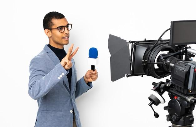 Reporter afroamericano uomo in possesso di un microfono e segnalazione di notizie su sfondo bianco isolato