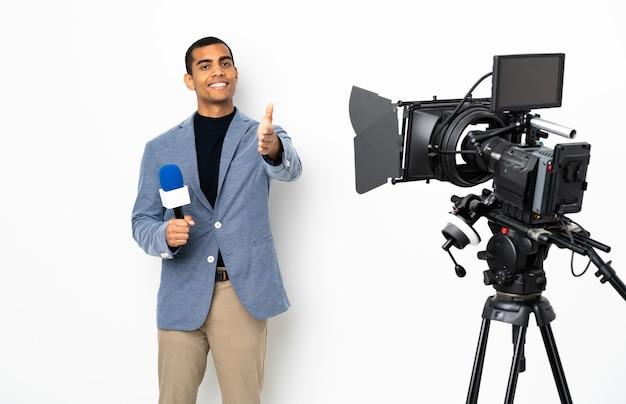 Reporter uomo afroamericano in possesso di un microfono e segnalazione di notizie su bianco isolato si stringono la mano per chiudere un buon affare