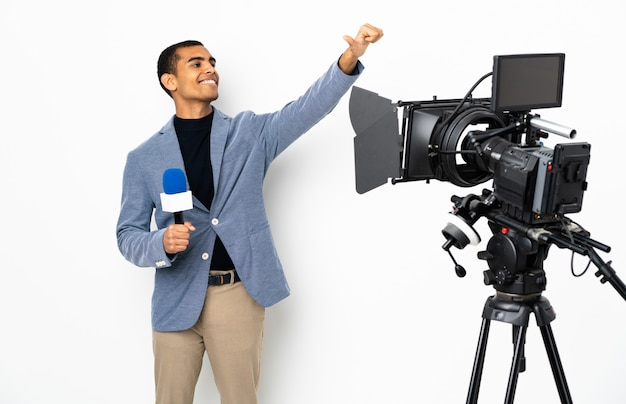 Uomo afroamericano reporter che tiene un microfono e che riferisce le notizie sopra la parete bianca isolata che dà un pollice in su gesto