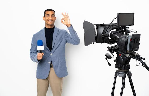 Uomo afroamericano del reporter che tiene un microfono e che riferisce le notizie sopra la parete bianca isolata che mostra segno giusto con le dita
