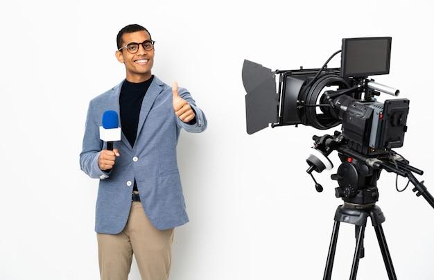Reporter uomo afroamericano in possesso di un microfono e riportare notizie su un muro bianco isolato con il pollice in alto perché è successo qualcosa di buono