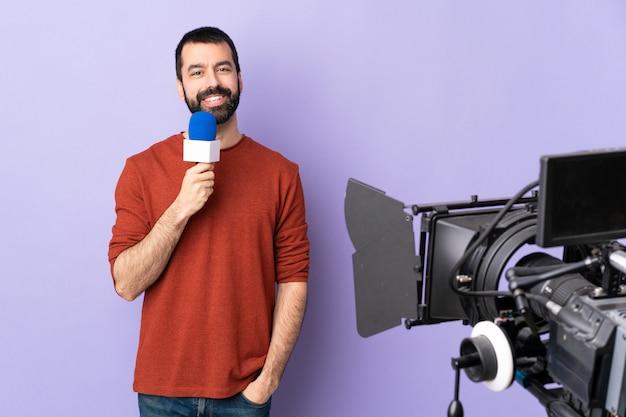 Uomo del reporter che tiene un microfono e che riferisce le notizie sopra la porpora isolata