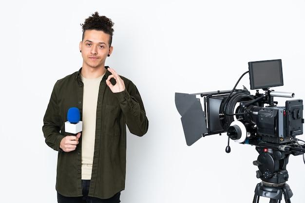 Uomo del reporter che tiene un microfono e che segnala le notizie che mostrano un segno giusto con le dita