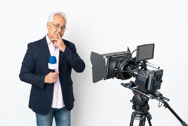 Reporter uomo brasiliano di mezza età che tiene un microfono e riporta notizie isolate su sfondo bianco pensando
