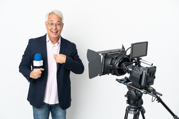 Reporter uomo brasiliano di mezza età che tiene un microfono e riporta notizie isolate su sfondo bianco con espressione facciale a sorpresa
