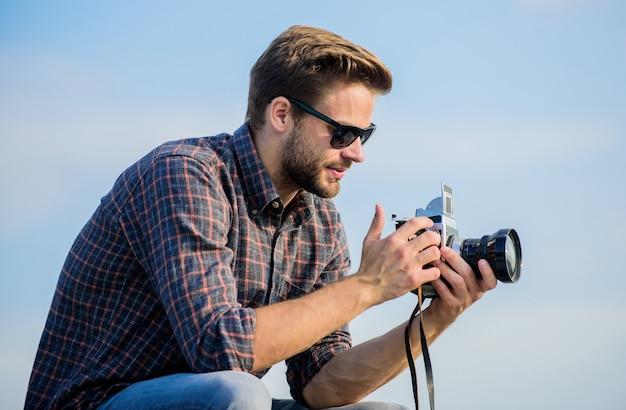 Reporter che scatta foto ragazzo all'aperto sullo sfondo del cielo blu attrezzatura vintage vlog di ripresa di blogger