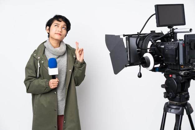 Reporter donna vietnamita in possesso di un microfono e riferire notizie con dita incrociate e augurando il meglio