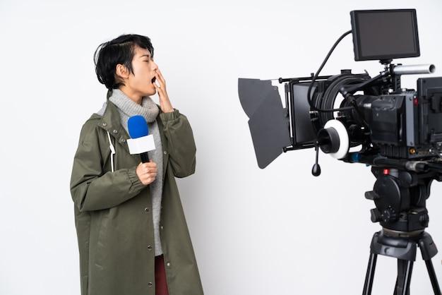 Donna vietnamita del reporter che tiene un microfono e che riferisce le notizie che sbadigliano e che coprono bocca spalancata di mano