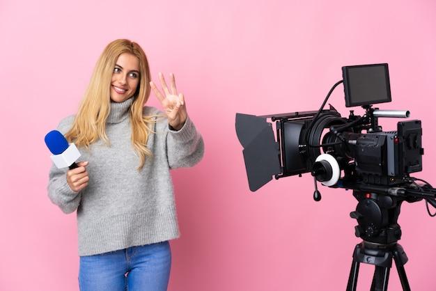 Reporter donna in possesso di un microfono e segnalazione di notizie sul muro rosa isolato felice e contando tre con le dita