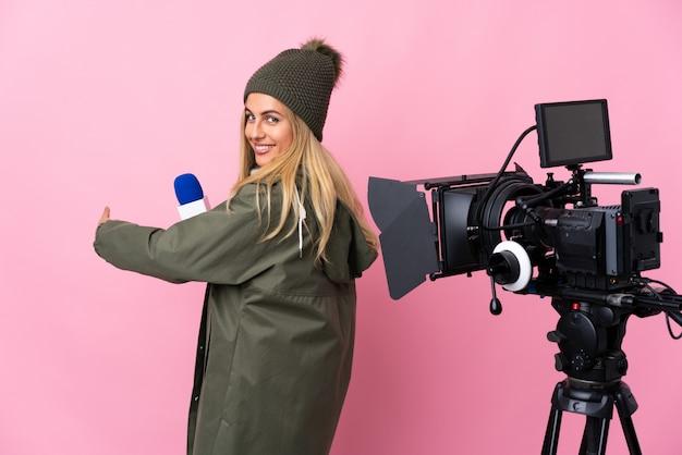 Donna del reporter che tiene un microfono e che riferisce le notizie sopra la parete rosa isolata che indica indietro