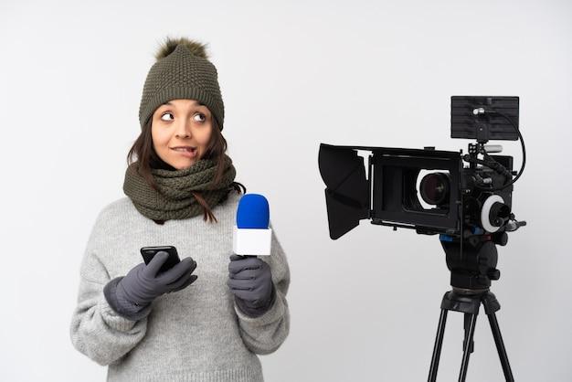 Reporter donna in possesso di un microfono e segnalare notizie su bianco isolato tenendo il caffè da portare via e un cellulare mentre si pensa a qualcosa