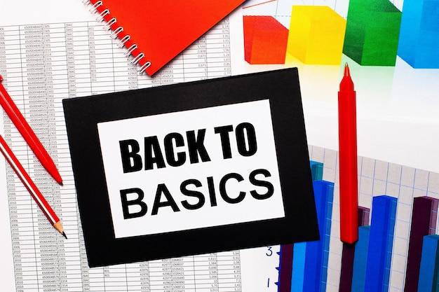 Rapporti e grafici a colori sono sul tavolo. ci sono anche penne rosse, matita e carta in una cornice nera con la scritta back to basics. vista dall'alto