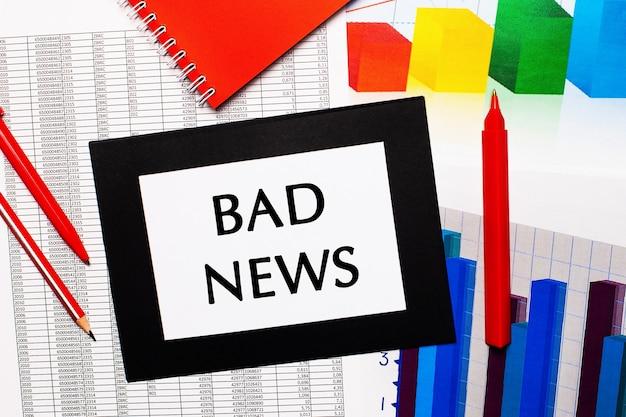 Rapporti e grafici a colori sono sul tavolo. ci sono anche penne rosse, matita e carta in una cornice nera con la scritta bad news. vista dall'alto