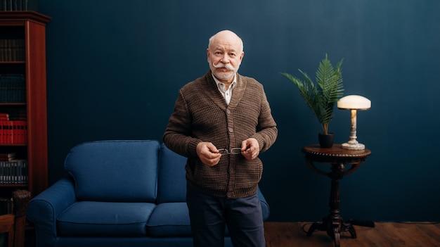 Rappresentante uomo anziano pone in ufficio a casa. barbuto anziano maturo in soggiorno, uomo d'affari di vecchiaia