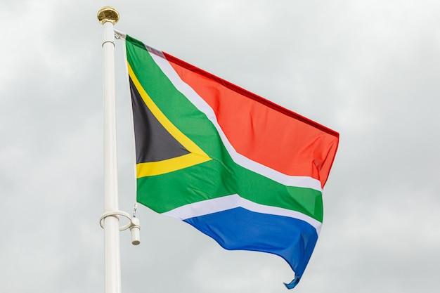 Bandiera della repubblica sudafricana contro il cielo nuvoloso bianco