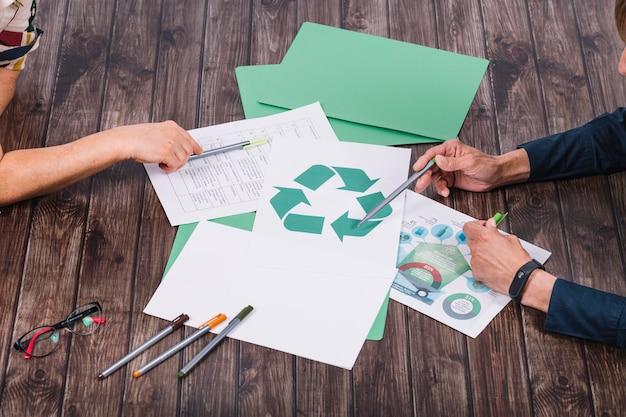 Squadra di salvataggio che fa discussione sullo scrittorio di legno di riciclaggio