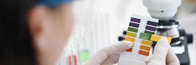 Il ricercatore tiene la striscia reattiva del ph per la ricerca
