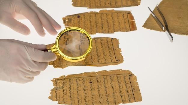 Il ricercatore studia la scrittura araba del corano usando una lente d'ingrandimento e un tavolo con una luce