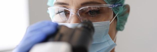 Il ricercatore indossa guanti e maschera protettiva guarda attraverso il microscopio.