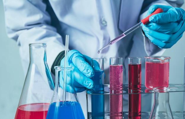 Ricercatore con le provette chimiche di vetro del laboratorio con liquido per il concetto di ricerca analitica, medica, farmaceutica e scientifica.