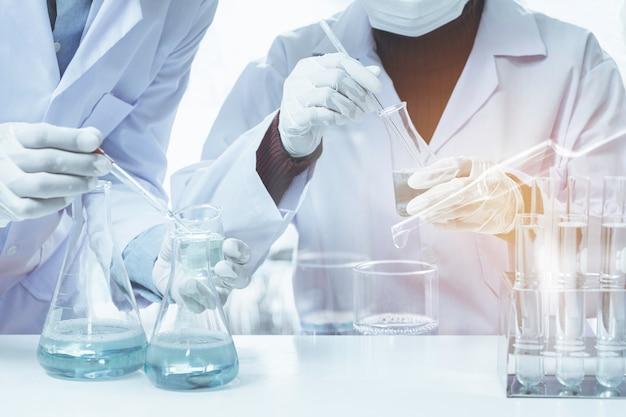 Ricercatore con provette chimiche da laboratorio in vetro con liquido per analisi