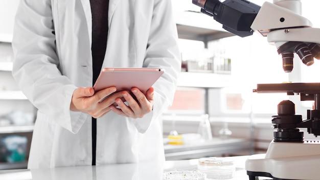 Ricercatore con tablet e microscopio nel laboratorio di biotecnologie