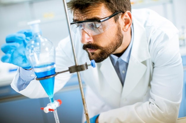 Ricercatore che lavora con liquido blu all'imbuto separatore in laboratorio