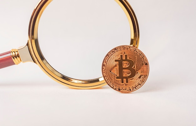 Ricerca e studio di btc o moneta bitcoin con lente d'ingrandimento su bianco.