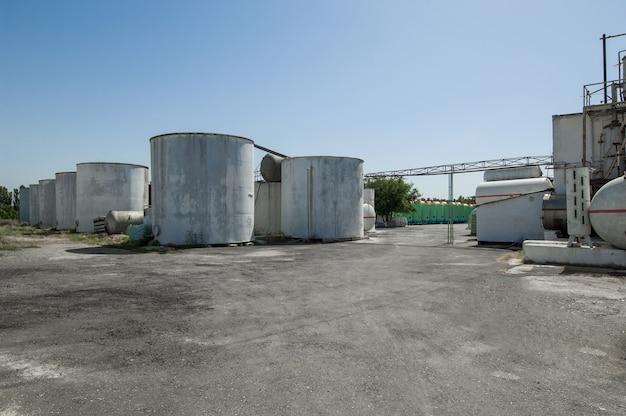 Serbatoio in fila e un edificio in una fattoria. impianto industriale pesante