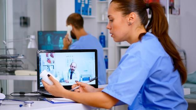 Medico residente che parla con il medico in videochiamata durante una riunione virtuale, ascoltando consigli medici e prendendo appunti. servizio sanitario a distanza, videoconferenza sulla salute, webinar online di telemedicina.