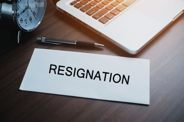 Lettera di dimissioni al dirigente su un tavolo di legno con penna e laptop. concetto di cessazione del rapporto di lavoro e dimissioni.