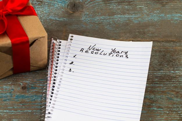Risoluzioni testo su carta per notebook con confezione regalo per il concetto di business.
